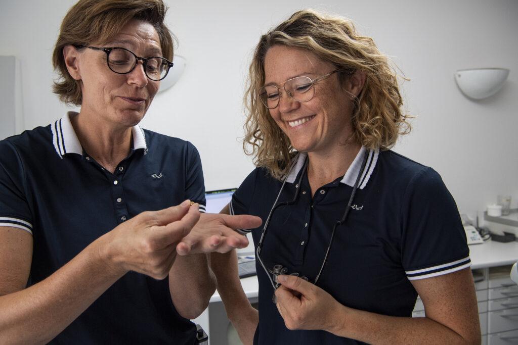 Tandlægerne Lene og Vibeke viser en tand.